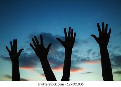 Four raised hands against twilight sky