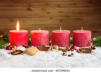 Four red advent candles with first candle lit and christmas decoration lying in snow as template