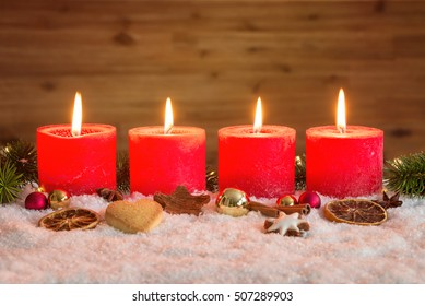 Four red advent candles with four candles lit and christmas decoration lying in snow as template