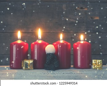 Four red Advent candles on a rustic wooden background, First candle is burning, Christmas concept background
