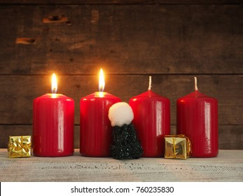 Four red Advent candles on a rustic wooden background, two candles burning, scond Advent, Christmas concept background