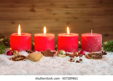 Four red advent candles with three candles lit and christmas decoration lying in snow as template