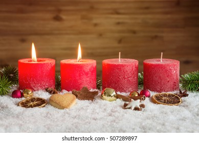 Four red advent candles with two candles lit and christmas decoration lying in snow as template