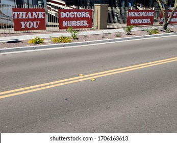 Four red banners on a fence stating Thank You Doctors, Nurses, Healthcare Workers, First Responders in support of those fighting the Novel Coronavirus Covid19 in the USA