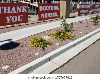 Four red banners on a fence stating Thank You Doctors, Nurses, Healthcare Workers, First Responders in support of those Americans fighting the Novel Coronavirus Covid19