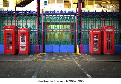 Four red booths in two different sizes with green, purple  and blue iron fence in background in Smithfield market in London UK