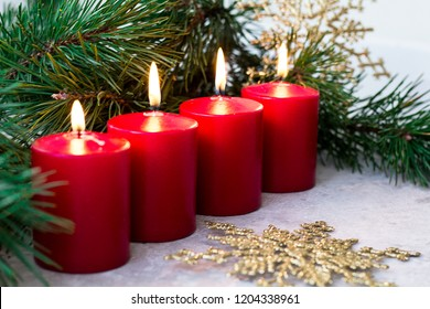 four red burning advent candles, golden snowflakes and a green spruce branch on a light background