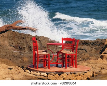 Four red traditional wooden chairs and one red table by the sea at Skyros island, Greece