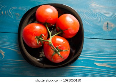 four red wet fresh tomatoes on a black plate on a wooden blue table/ kitchen