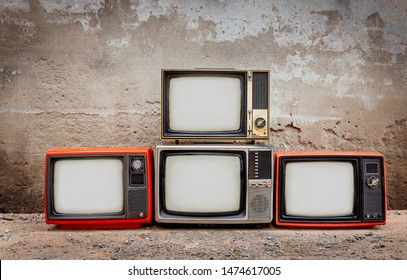Four retro old television pile on the floor. Four old TVs placed in front of the old cement wall. Antique , Vintage filtered style