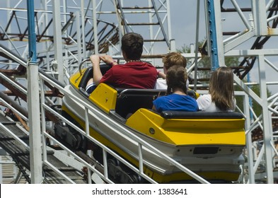 Four riders on an old roller coaster