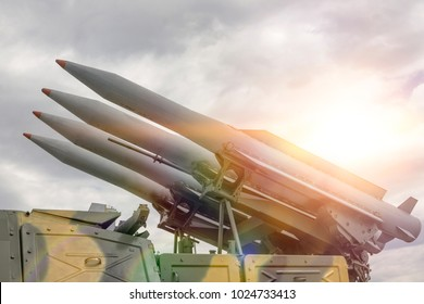 Four rockets are directed upwards against a dramatic sky in the sun. Weapons of mass destruction, nuclear warhead, chemical charge.