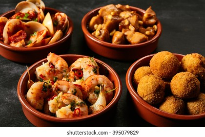 Four round ceramic red bowls of Spanish appetizers knowns as tapas with seafood, nuts and sauces