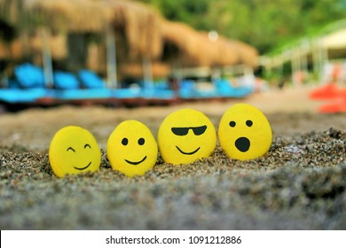 Four round pebbles painted as Emoticons or emojis with different expressions placed in a line on a sunny and sandy beach with sunbeds in the background.