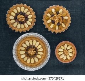 Four round traditional Polish Easter cakes with almonds, raisins and walnuts on the dark background.