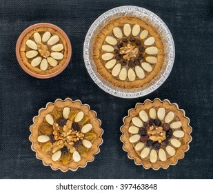"""Four round traditional Polish Easter cakes """"Mazurek"""" with almonds, raisins and walnuts on the dark fabric background."""