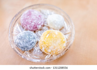 Four round whole mochi glutinous rice cake dessert pieces colorful multicolored natural food dye wagashi daifuku filled with ice cream