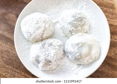 Four round whole mochi sticky glutinous rice cake dessert pieces, wagashi daifuku filled with ice cream or red bean adzuki jam filling