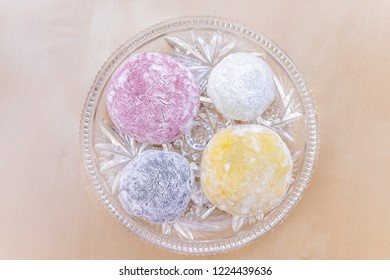Four round whole mochi sticky glutinous rice cake dessert pieces, colorful multicolored natural food dye wagashi daifuku filled with ice cream