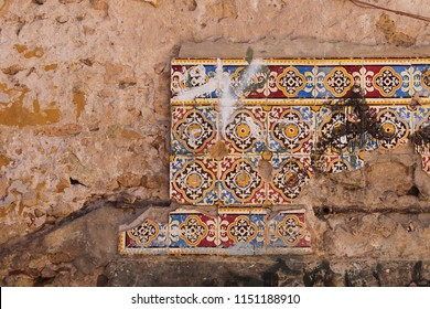 Four rows of a partly broken traditional ceramics tiles on a damaged wall of an old house. El Jadida, Morocco.