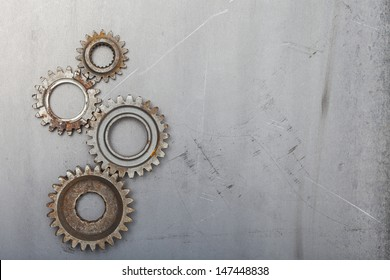 Four rusty gears on a steel background with room for your copy.