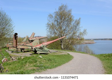 Four rusty green cannons from the Russian period point out over the water from Suomenlinna sea fortress