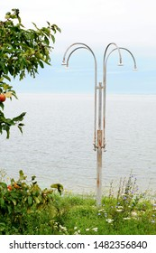 Four rusty, not working shower heads stand on the shore of the lake on a summer day, there is not a soul around.