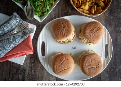Four sandwiches on a white platter with salad and french fries