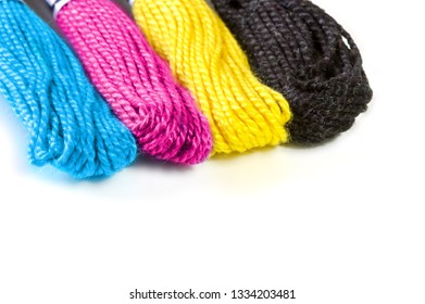 Four sawing silk threads in the prepress colors cmyk with white copy space for text.