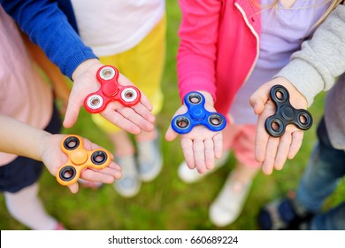 Four school children playing with colorful fidget spinners on the playground. Popular stress-relieving toy for school kids and adults.