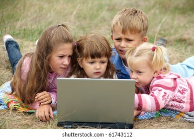 four schoolchild lying on green meadows and exercise on a laptop