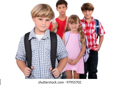 Four schoolchildren with backpacks