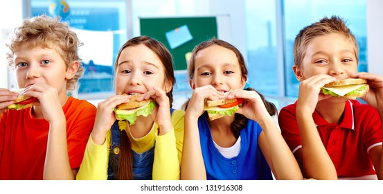 Four schoolkids looking at camera while having lunch during break