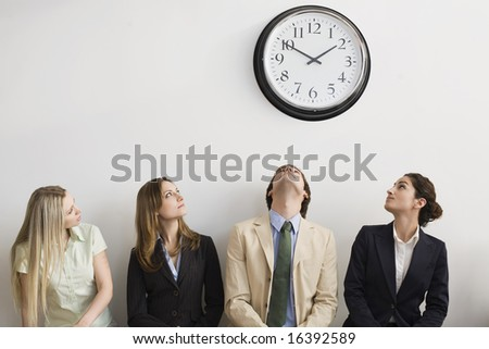 four seated office workers looking clock stock photo edit now