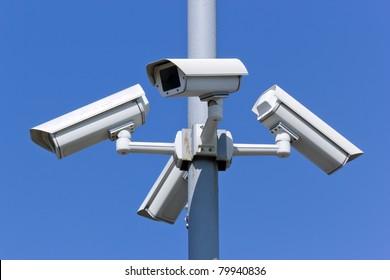 four security cameras on blue sky