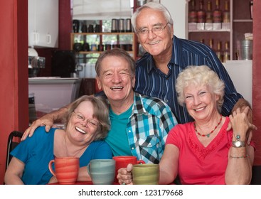 Four senior citizens laughing together in cafe