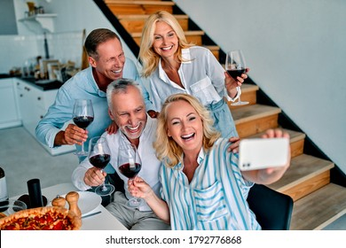 Four senior friends having dinner at home. Two handsome mature men and two attractive women spending time together indoors. Group of old friends drinking wine in modern apartment.
