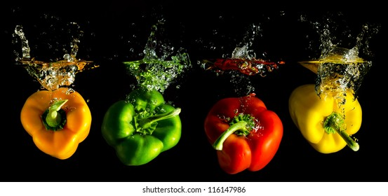 four several coloured paprika falling into water before black background