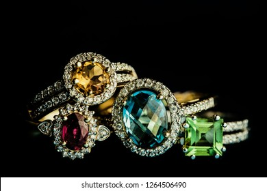 Four shiny golder rings with precious gems isolated on black.