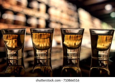 Four shots of whiskey alcohol on the bar at a distillery low angle dark amber tones.