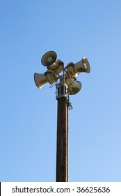 Four sirens on a pole with blue sky in the background.