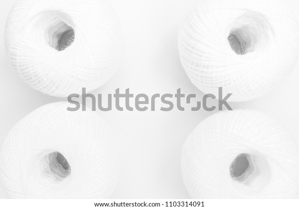 four skeins of white thread on white background, close-up abstract background