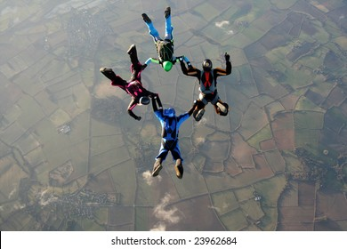 Four skydivers doing formations