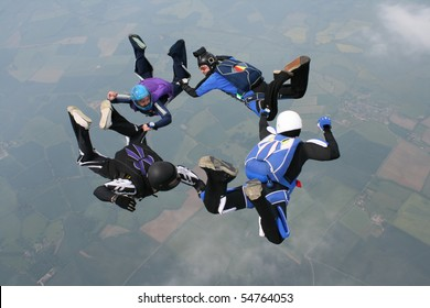 Four skydivers form a circle