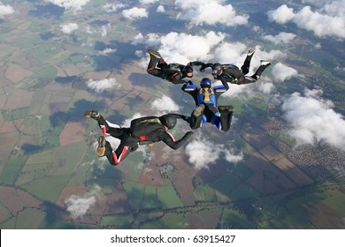 Four skydivers in freefall on a sunny day