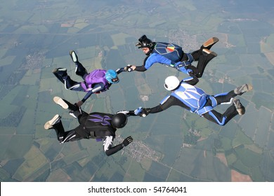 Four skydivers holding hands