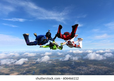 Four skydivers in the sky. Side view.