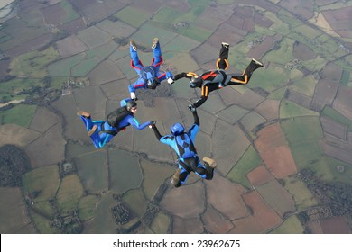 Four skydivers in a start formation