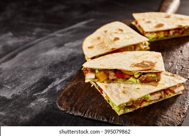 Four sliced wedges of meat and veggie filled quesadillas on worn out black cutting board over dark background with copy space