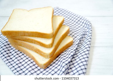 Four of sliced white bread on the table. Good for breakfast. Soft. Copy space.